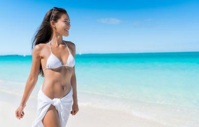 Femme asiatique marchant sur la plage en maillot de bain et paréo